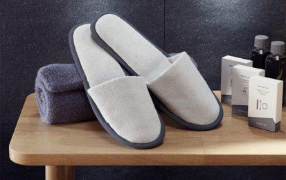 Holzbank auf der ein eingerolltes Handtuch liegt auf dem Velours Slipper geschlossen stehen mit 3 Kartons der Design Line Grey einmal das Vanity Kit das Shower Cap, Sewing Kit