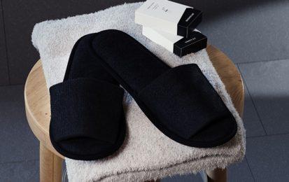 Frottee Slipper offen auf einem Handtuch mit 2 Ameneties Kartons Design Line Black die auf einem Hocker im Bad stehen.